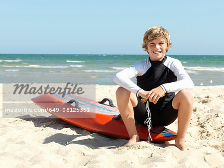 Portrait of confident boy nipper (child surf life savers) sitting on surfboard at beach, Altona, Melbourne, Australia Stock Photo - Premium Royalty-Free, Image code: 649-08125351