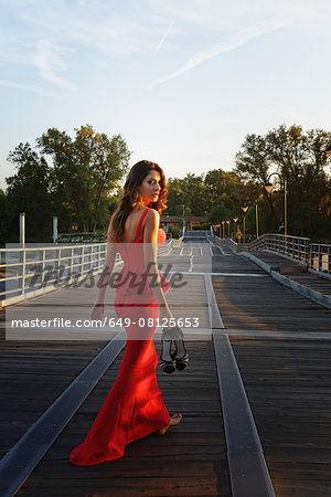 Portrait of a young woman in a smart red dress walking away and looking over shoulder Stock Photo - Premium Royalty-Free, Image code: 649-08125653