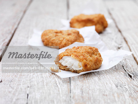 Three fried breaded chunky cod pieces on wooden table Stock Photo - Premium Royalty-Free, Image code: 649-08125692