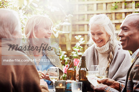 Senior friends playing cards in garden Stock Photo - Premium Royalty-Free, Image code: 649-08125765