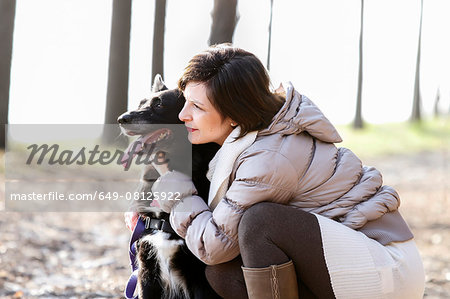 Mid adult woman crouching with her dog on dirt path Stock Photo - Premium Royalty-Free, Image code: 649-08125922