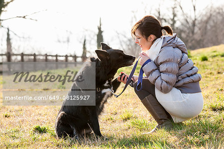 Mid adult woman training her dog to hold up paw in field Stock Photo - Premium Royalty-Free, Image code: 649-08125927