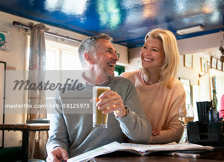 Couple laughing and reading newspaper in pub Stock Photo - Premium Royalty-Free, Image code: 649-08125973