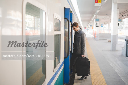 Young businessman commuter boarding train with suitcase. Stock Photo - Premium Royalty-Free, Image code: 649-08144791