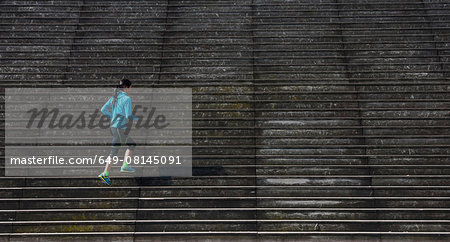 Mature female runner running diagonally up wooden stairway Stock Photo - Premium Royalty-Free, Image code: 649-08145091