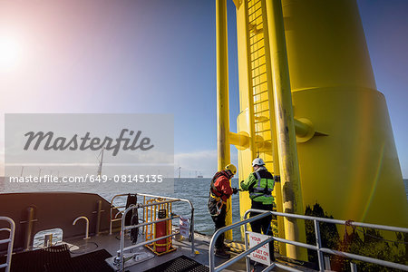 Engineers climbing wind turbine at offshore wind farm Stock Photo - Premium Royalty-Free, Image code: 649-08145135
