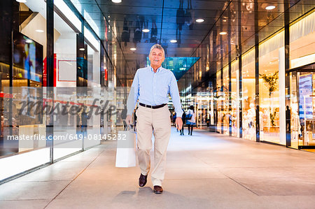 Senior man walking through shopping mall holding bag Stock Photo - Premium Royalty-Free, Image code: 649-08145232