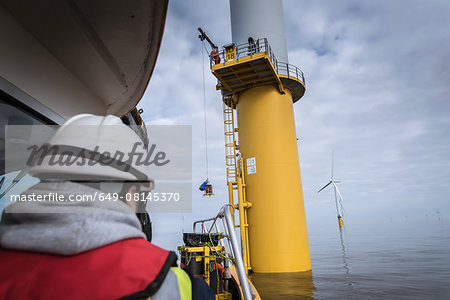 Engineers winching parts up to wind turbine on offshore windfarm Stock Photo - Premium Royalty-Free, Image code: 649-08145370