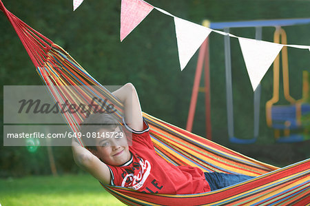 Portrait of confident boy reclining in striped garden hammock with hands behind head Stock Photo - Premium Royalty-Free, Image code: 649-08145729