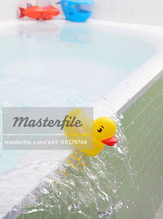 Rubber duck falling out of bath overflowing with water Stock Photo - Premium Royalty-Free, Image code: 649-08179748