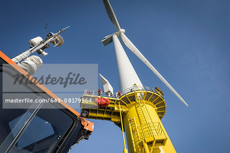 Engineers climbing wind turbine from boat at offshore windfarm, low angle view Stock Photo - Premium Royalty-Free, Image code: 649-08179964