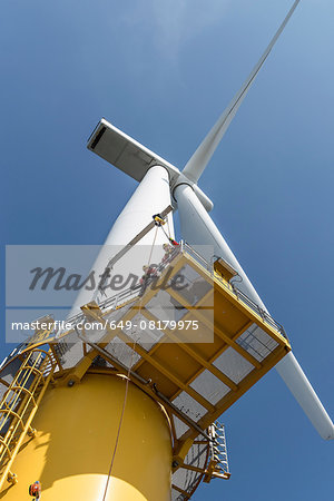 Engineers climbing wind turbine from boat at offshore windfarm, low angle view Stock Photo - Premium Royalty-Free, Image code: 649-08179975
