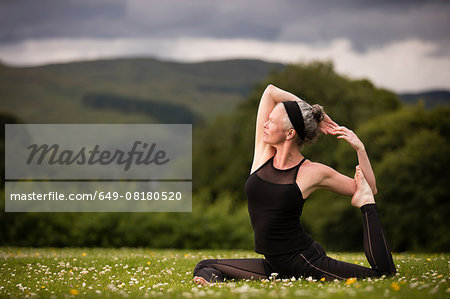 Mature woman doing splits practicing yoga in field Stock Photo - Premium Royalty-Free, Image code: 649-08180520