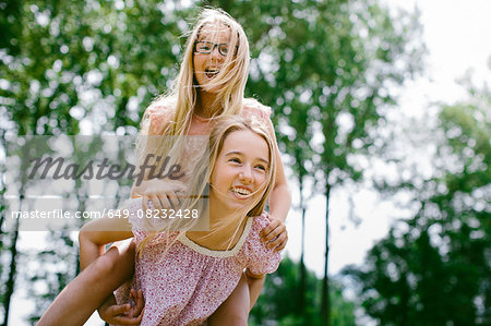 Young girl giving sister a piggyback ride Stock Photo - Premium Royalty-Free, Image code: 649-08232428