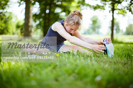 Young girl in park, doing stretches on grass Stock Photo - Premium Royalty-Free, Image code: 649-08232442