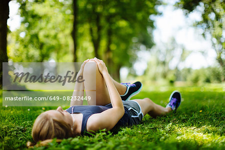 Young girl in park, lying on grass, stretching legs Stock Photo - Premium Royalty-Free, Image code: 649-08232449