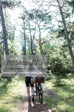 Mature woman pushing bicycle with foraging baskets on forest path Stock Photo - Premium Royalty-Free, Image code: 649-08232805