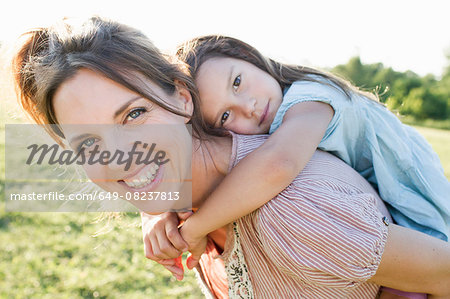 Mature woman giving daughter piggy back ride in park Stock Photo - Premium Royalty-Free, Image code: 649-08237813