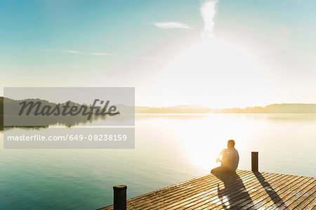 Young man sitting on corner of pier of sunlit lake, Woerthsee, Bavaria, Germany Stock Photo - Premium Royalty-Free, Image code: 649-08238159
