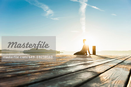 Young man sitting on pier of sunlit lake, Woerthsee, Bavaria, Germany Stock Photo - Premium Royalty-Free, Image code: 649-08238160