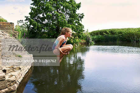 Side view of girl jumping into lake Stock Photo - Premium Royalty-Free, Image code: 649-08238762