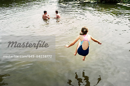 Rear view of girl jumping into lake Stock Photo - Premium Royalty-Free, Image code: 649-08238772