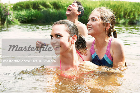 Two sisters and friend swimming in rural lake Stock Photo - Premium Royalty-Free, Image code: 649-08238774