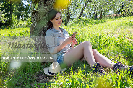 Young woman sitting leaning against tree using smartphone looking down smiling Stock Photo - Premium Royalty-Free, Image code: 649-08239067