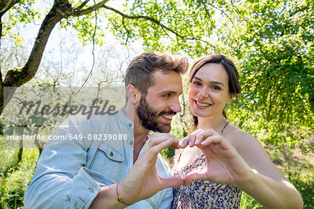 Young couple making heart shape with hands, looking at camera smiling Stock Photo - Premium Royalty-Free, Image code: 649-08239088