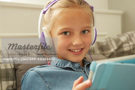 Girl wearing headphones holding digital tablet looking at camera smiling Stock Photo - Premium Royalty-Free, Image code: 649-08306400