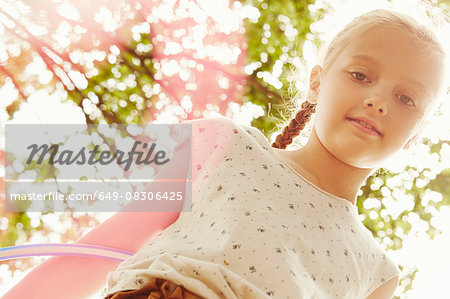 Low angle view of girl playing with hula hoop looking at camera smiling Stock Photo - Premium Royalty-Free, Image code: 649-08306425