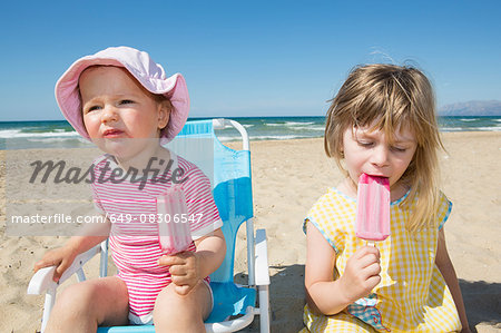 Female toddler and sister eating ice lollies on beach Stock Photo - Premium Royalty-Free, Image code: 649-08306547