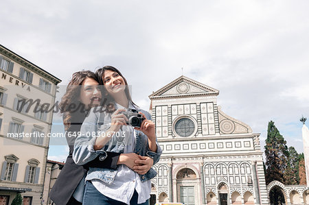 Lesbian couple holding digital camera hugging in front of church, Piazza Santa Maria, Novella Florence, Tuscany, Italy Stock Photo - Premium Royalty-Free, Image code: 649-08306703