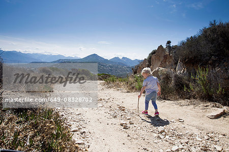 Female toddler on dirt track with walking stick, Calvi, Corsica, France Stock Photo - Premium Royalty-Free, Image code: 649-08328702