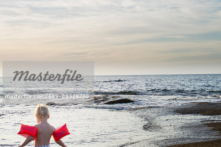 Rear view of female toddler wearing inflatable armbands at coast, Calvi, Corsica, France Stock Photo - Premium Royalty-Free, Image code: 649-08328720