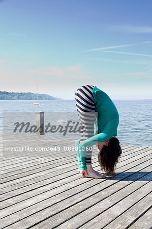 Side view of mature woman on pier by ocean bending over holding ankles Stock Photo - Premium Royalty-Free, Image code: 649-08381060