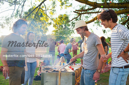 Happy adult friends barbecuing at sunset party in park Stock Photo - Premium Royalty-Free, Image code: 649-08381087