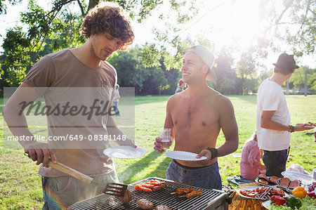 Young men barbecuing at sunset park party Stock Photo - Premium Royalty-Free, Image code: 649-08381148