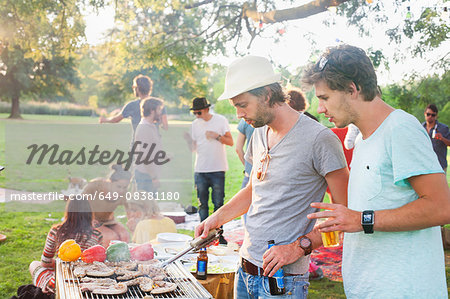 Young men barbecuing at group party in park Stock Photo - Premium Royalty-Free, Image code: 649-08381180