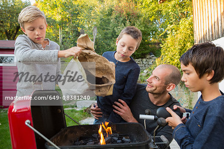 Mid adult man and sons preparing barbecue in garden Stock Photo - Premium Royalty-Free, Image code: 649-08381240