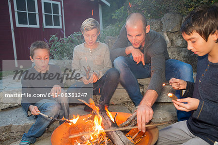 Father and three sons sitting by garden campfire at dusk Stock Photo - Premium Royalty-Free, Image code: 649-08381247