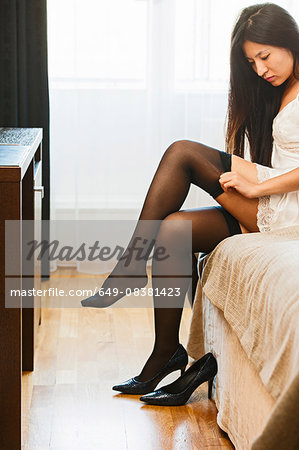 Mid adult woman sitting on edge of bed, putting on stockings Stock Photo - Premium Royalty-Free, Image code: 649-08381423