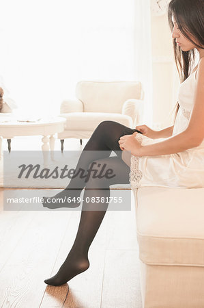 Beautiful woman putting on black stockings in hotel suite Stock Photo - Premium Royalty-Free, Image code: 649-08381755
