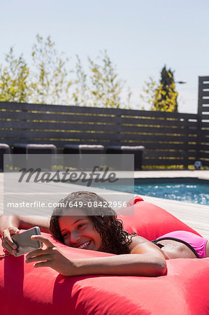 Girl lying on poolside cushion reading smartphone, Cassis, Provence, France Stock Photo - Premium Royalty-Free, Image code: 649-08422956