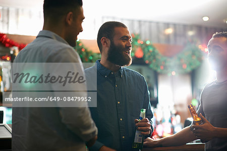 Young men in public house holding beer bottles leaning against counter smiling Stock Photo - Premium Royalty-Free, Image code: 649-08479952
