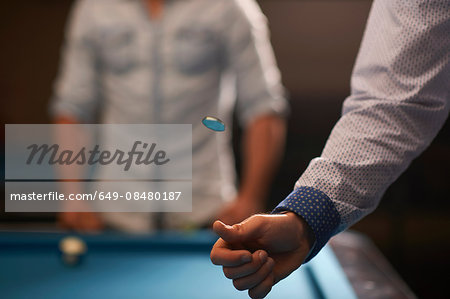 Man tossing coin at pool table Stock Photo - Premium Royalty-Free, Image code: 649-08480187