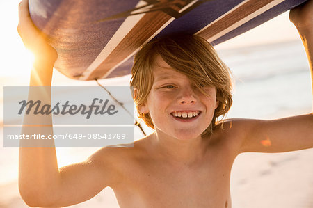 Boy carrying surfboard over head smiling Stock Photo - Premium Royalty-Free, Image code: 649-08543789