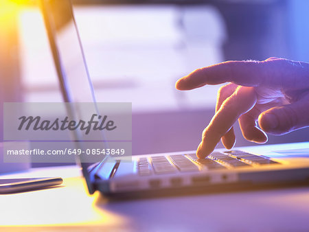 Man working online at a laptop computer Stock Photo - Premium Royalty-Free, Image code: 649-08543849