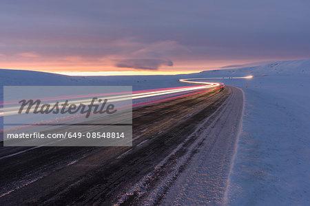 Light trails along road on snow covered landscape at sunset, Mosfellsheidi, Iceland