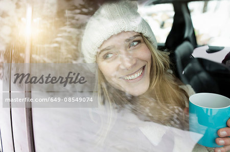 Woman having coffee inside vehicle Stock Photo - Premium Royalty-Free, Image code: 649-08549074